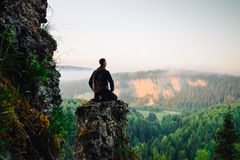 Man sitting on the top of the mountain in yoga pose. Meeting sunrise royalty free stock photo