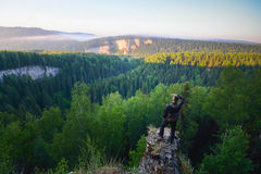 Man sitting on the top of the mountain in yoga pose. Man standing on the top of the mountain, leisure in harmony with nature stock photos
