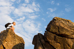 Man sitting on top of a rocky mountain Stock Photography