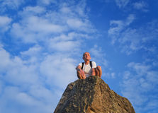 Man sitting on top of a rocky pinnacle. Man wearing a rucksack sitting on top of rocky pinnacle mountain peak enjoying the solitude surveying the surrounding stock photography