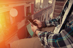 Man sitting on the top of the roof with mobile phone in his hand. Brave man sitting on the top of the roof with mobile phone in his hand Royalty Free Stock Images