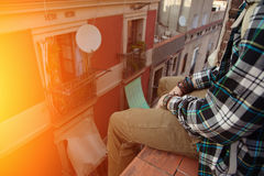 Man sitting on the top of the roof and relaxing. Brave man sitting on the top of the roof and relaxing Stock Photo