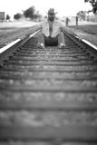 Man sitting on the tracks. Man sitting barefoot between thetracks Royalty Free Stock Images