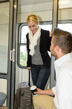Man sitting train compartment woman getting in. Man sitting train compartment women getting in commuters smiling luggage Royalty Free Stock Photography
