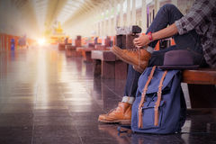 Man sitting .travel bag at the train station.vintage filter effe. Cted. side view Stock Photo
