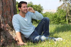 Man sitting by a tree Royalty Free Stock Images