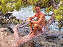 Man sitting on tree - Phaselis bay - Çamyuva, Kemer, coast and beaches of Turkey Royalty Free Stock Photography