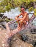 Man sitting on tree - Phaselis bay - Çamyuva, Kemer, coast and beaches of Turkey Royalty Free Stock Images