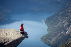 Man sitting on trolltunga rock in norway stock photography