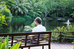 Man sitting in Tropical Location and Working Royalty Free Stock Photos