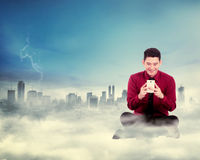 Man sitting typing with cellphone on the cloud Stock Images