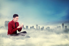Man sitting typing with cellphone on the cloud Royalty Free Stock Photos