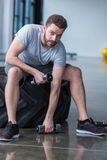Man sitting on tyre and exercising with small dumbbells Stock Photos