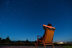 Man sitting under the stars. Man sitting in armchair under the stars Stock Photography