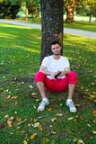 Man sitting under a tree. With a book Royalty Free Stock Images