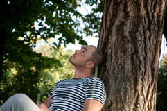 Man sitting under a tree Stock Photography