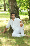 Man sitting under a tree. Man in white sitting under a tree Stock Image