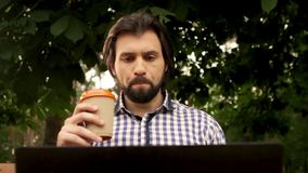 Man is sitting under trees and holding laptop. He starts to smile and take cup of coffee and drinking. Man looks serious. He is looking down and to screen stock video