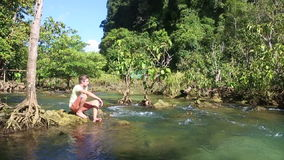 Man sitting under which clear water mangrove roots stock video footage