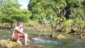 Man sitting under which clear water mangrove roots stock footage