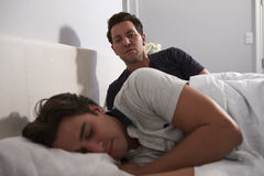 Man sitting up in bed, looking while his boyfriend sleeps Stock Photo