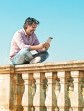 Man sitting and using digital tablet outdoors Royalty Free Stock Photography