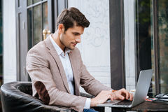 Man sitting and using laptop in outdoor cafe. Concentrated young man sitting and using laptop in outdoor cafe Royalty Free Stock Photos