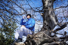 Man sitting on  a venerable tree and drinking water Stock Photography