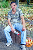 Man sitting waiting on a tree stump Stock Photos