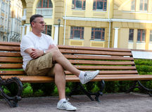 Man sitting waiting on an urban bench. Casual middle-aged man sitting waiting on a wooden bench in an urban environment Stock Photography