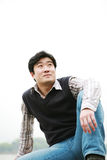 Man sitting on wall. Young asian man sitting on wall Stock Images