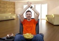 Man Sitting and Watching Football At Home Stock Photo