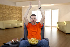 Man Sitting and Watching Football At Home Stock Image