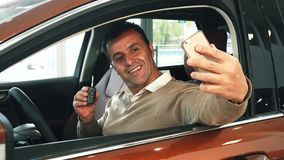 A cheerful man sitting in the car makes selfie with keys