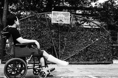 Man sitting on wheel chair with broken leg Stock Images