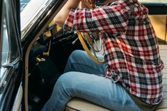 The man is sitting at the wheel, the driver. view from the rear window. Rear view of tourist guy in car. Travel and summer stock photography