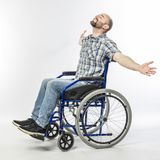 Man on wheelschair. Man sitting in a wheelchair with arms raised and eyes closed. smiling and positive expression royalty free stock photo