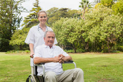 Man sitting in a wheelchair with his nurse pushing him Stock Photography