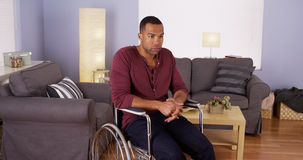 Man sitting in wheelchair looking at camera Stock Images