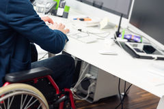 Man Sitting In Wheelchair Working In Modern Office Royalty Free Stock Photo