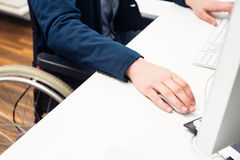 Man Sitting In Wheelchair Working In Modern Office Royalty Free Stock Image