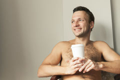 Man sitting with white paper cup of Coffee. Portrait of young happy European man sitting with white paper cup of Coffee Stock Photography