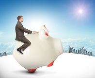 Man sitting on white piggy bank, side view. Businessman sitting on piggy bank on nature background Stock Photo