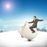 Man sitting on white piggy bank, side view. Businessman sitting on piggy bank on nature background Royalty Free Stock Photography