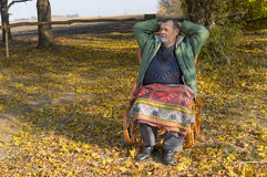 Man sitting in wicker chair at sunny autumnal day Stock Image