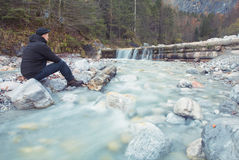 Man sitting in the  wild on a brook Royalty Free Stock Images