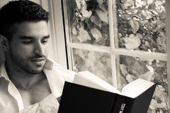 Man in sitting on window ledge with open shirt and pecs reading hardback book. Handsome, man with open white shirt and pecs reading hardback book in bay window stock photos