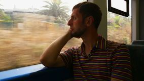 Man sitting by window and looking at changing landscape from fast moving train. Stock footage stock footage