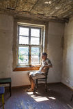 Man sitting at the window of an old house Royalty Free Stock Image
