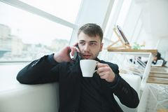 The man is sitting by the window and talking on the phone with a cup of hot coffee in his hands. Royalty Free Stock Photography